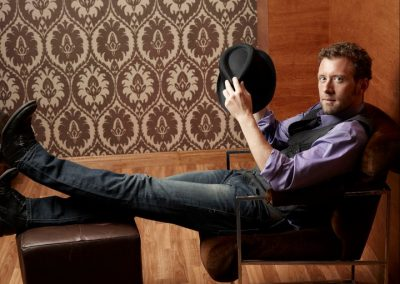 TJ Thyne in a vest and hat, reclining