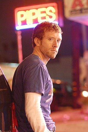 Image of TJ Thyne in his city, Los Angeles, with a neon sign with the word pipes.