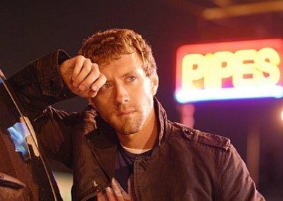 Image of TJ Thyne in his city, Los Angeles, leaning on a car with a neon sign with the word pipes in the background.