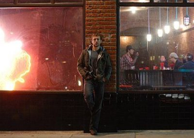 Image of TJ Thyne leaning against a wall outside of a bar from his TJ in his city Los Angeles photoshoot
