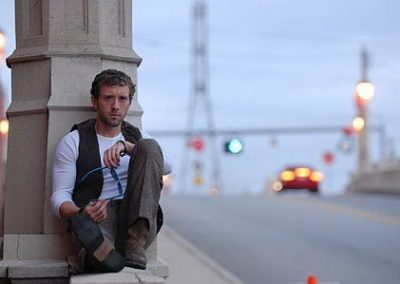 Image of TJ Thyne sitting next to a road from his TJ in his city Los Angeles photoshoot