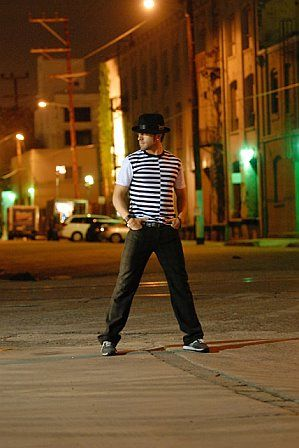 Full length image of TJ Thyne in his city, Los Angeles, wearing a hat and zebra striped shirt.