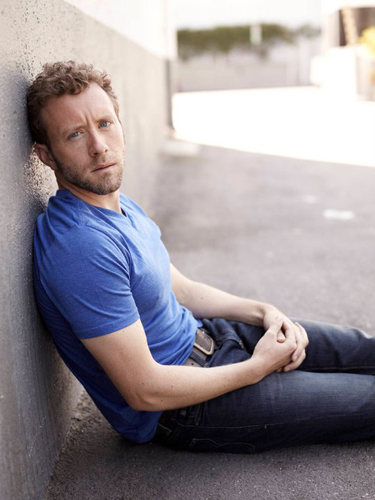 TJ-Thyne-Blue-t-shirt--sitting-leaning-wall-photo4