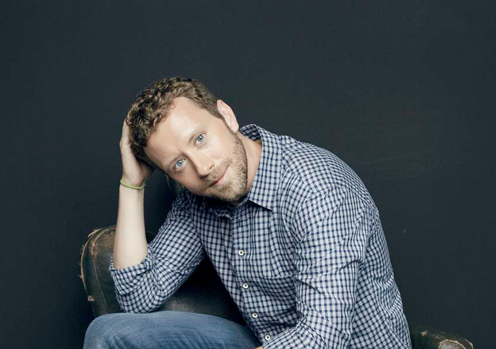 TJ Thyne in casual plaid shirt, sitting in relaxed pose