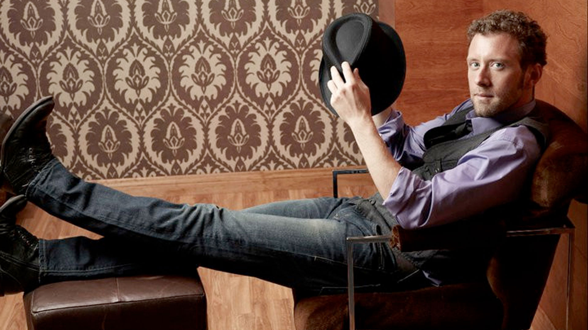 TJ Thyne lounging in purple shirt and grey vest, holding a fedora hat