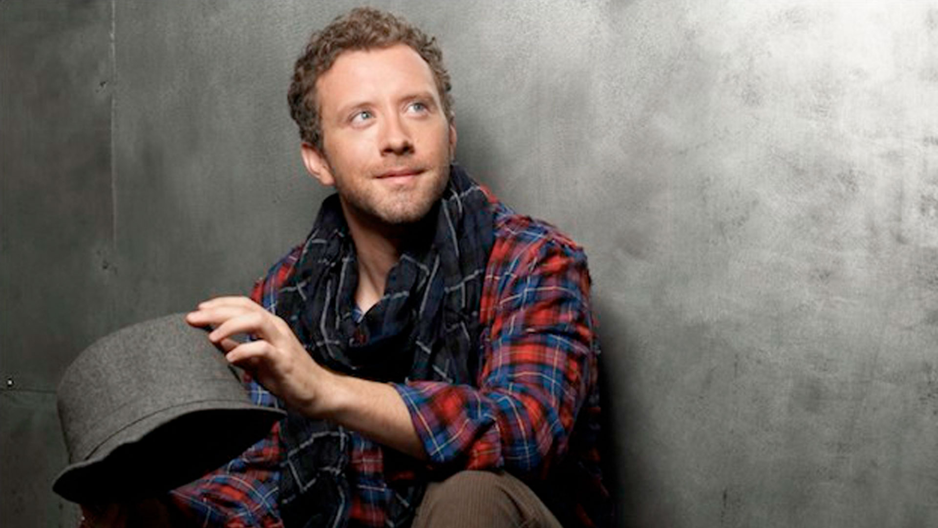 TJ Thyne photoshoot image, wearing plaid shirt, plaid scarf and grey hat, sittng against a wall